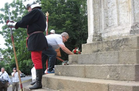 Laying flowers at Queen Eleanor's Cross